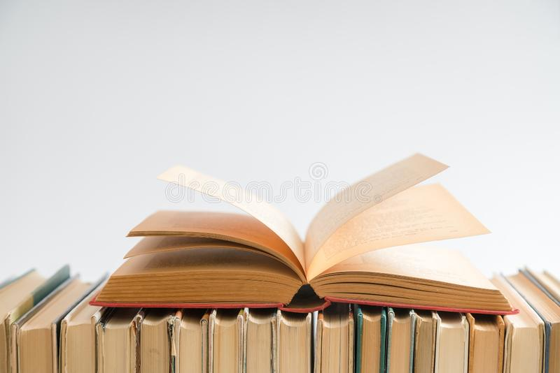 Open book on white background, hardback books on wooden table. E. Ducation and learning background. Back to school, studying. Copy space for text stock image