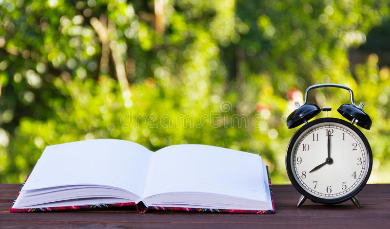 Open book with white pages and clocks. Black alarm clock and a notebook. Copy space stock photo
