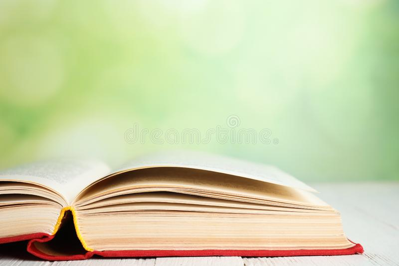 Open book on white table against blurred green background, closeup. Space for text. Open book on white wooden table against blurred green background, closeup royalty free stock photography