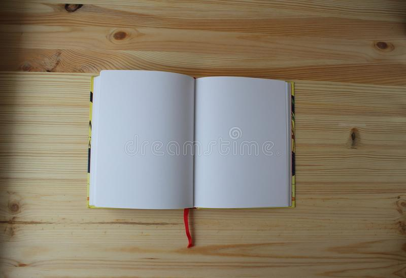 The workbook is open. The open book is on a wooden background royalty free stock photo