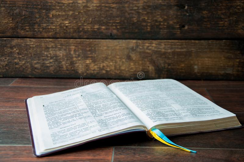 An open book on a wooden table. Bible on wooden background royalty free stock images