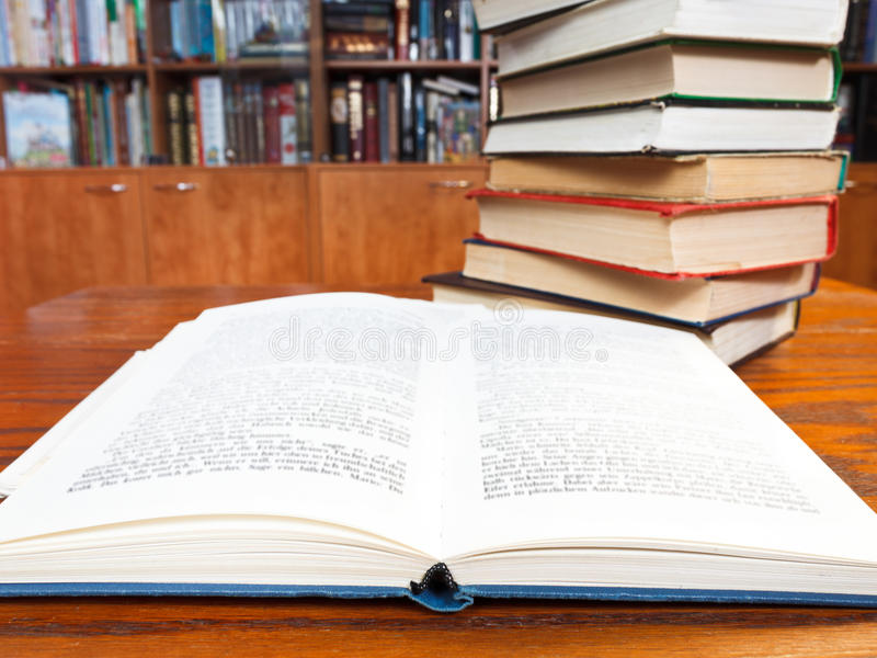 Open book on wooden table. Open book with blur font close up on wooden table near bookcases royalty free stock photography