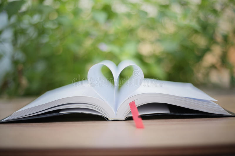 Open book on wooden table on natural background. Heart book page royalty free stock photos