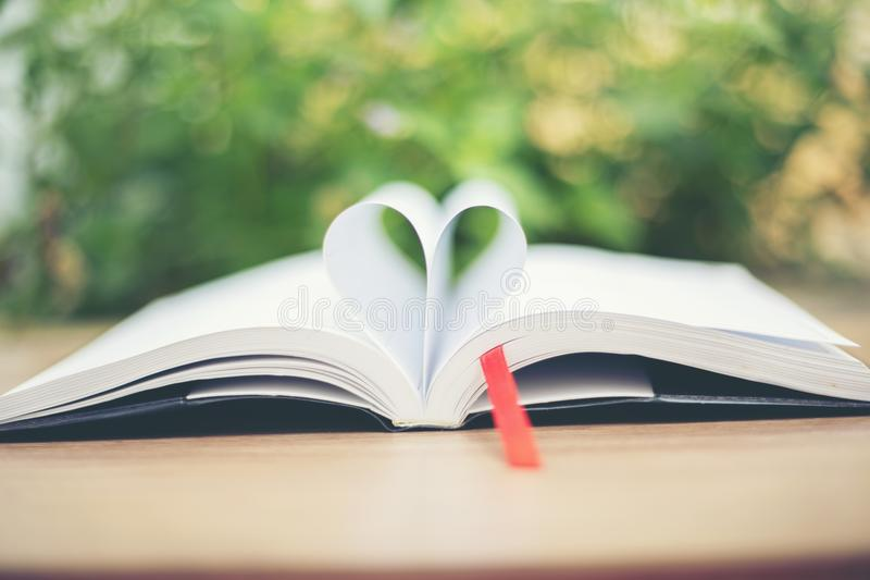 Open book on wooden table on natural background. Heart book page stock images