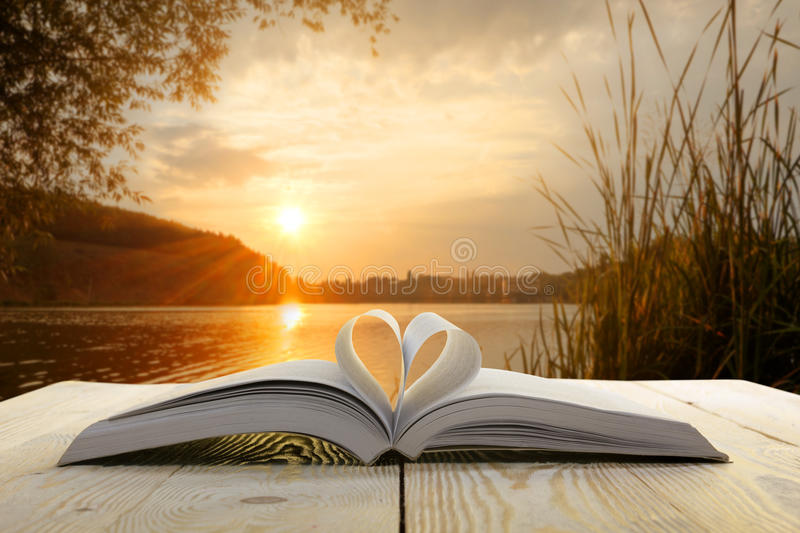 Open book on wooden table on natural blurred background. Heart book page. Back to school. Copy Space.  royalty free stock images