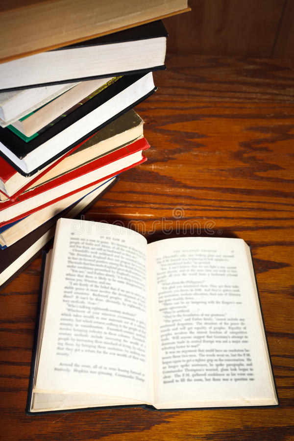 Open book on wooden table. Stack of books and open book with blur font on wooden table stock images