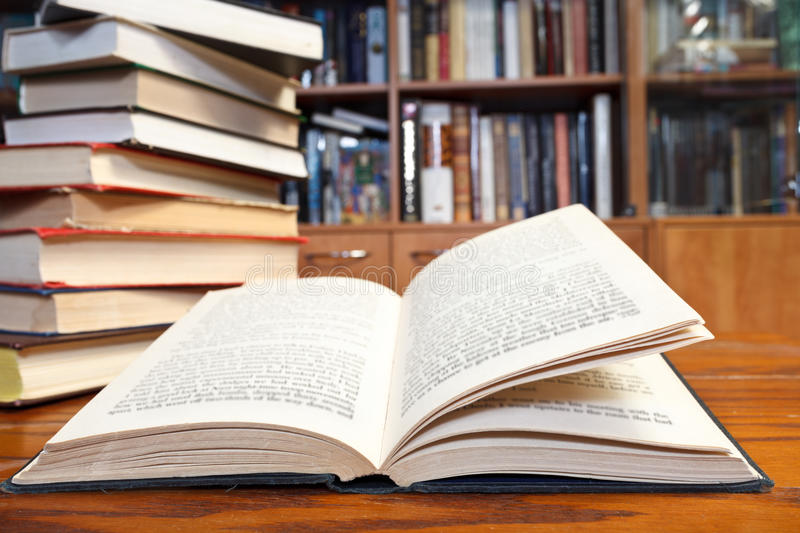 Open book on wooden table. Stack of books and open book with blur font close up on wooden table near bookcases royalty free stock image