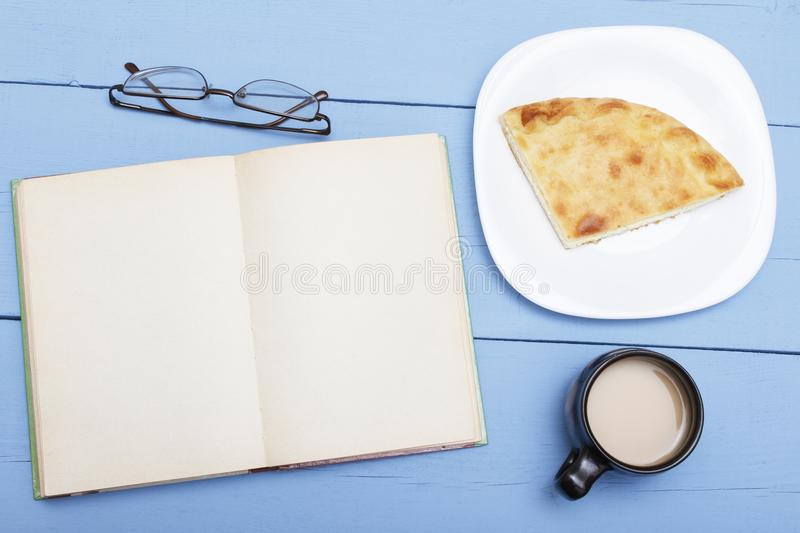 Open book on wooden table with white page, cup coffee with milk and pie. Sketch for copy space or design. Concept education stock images