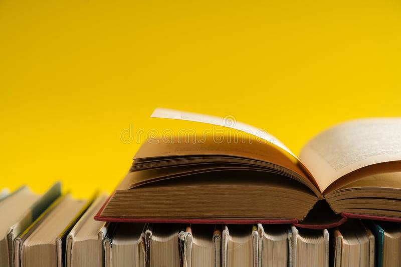 Open book on yellow background, hardback books on wooden table. Education and learning background. Back to school, studying. Copy space for text royalty free stock photos