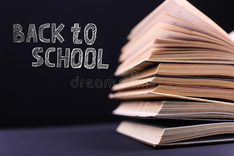 Open books are stacked on the desk, on a black background, isolate. Difficult homework at school, a mountain of knowledge. Open books are stacked on the desk, on royalty free stock photography