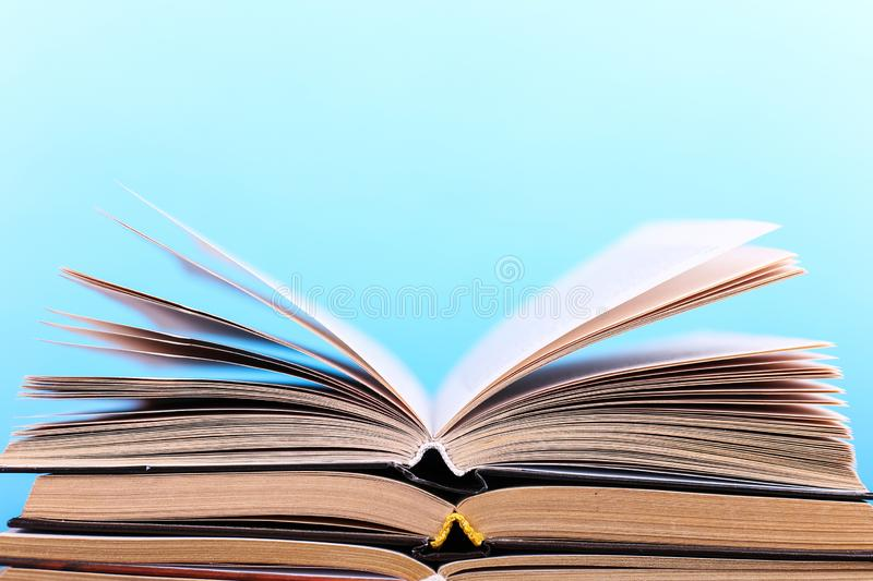 Open books are stacked on the desk, on a blue background. Difficult homework at school, a mountain of knowledge stock photo