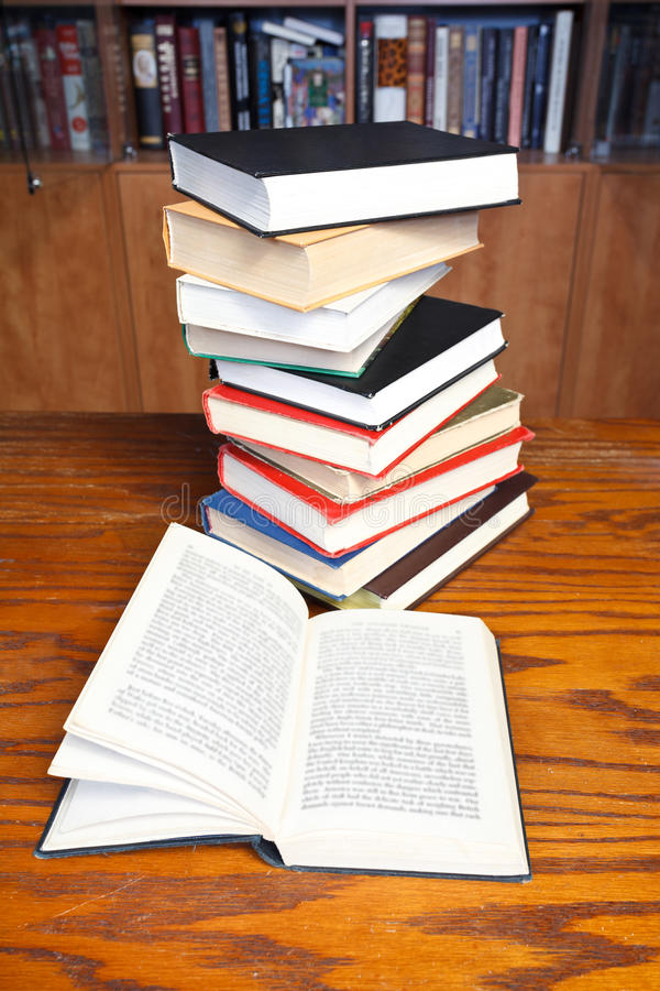 Open books on wooden table. Stack of books and open book with blur font on wooden table near bookcases stock photo
