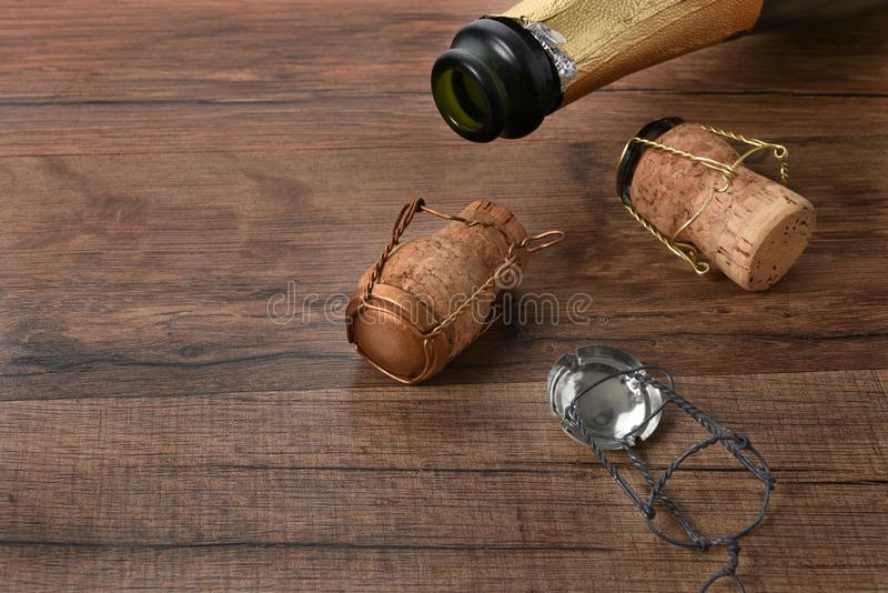 Open bottle of champagne with corks on a wood table with copy space. High angle shot of an open bottle of champagne with corks on a wood table with copy space stock images