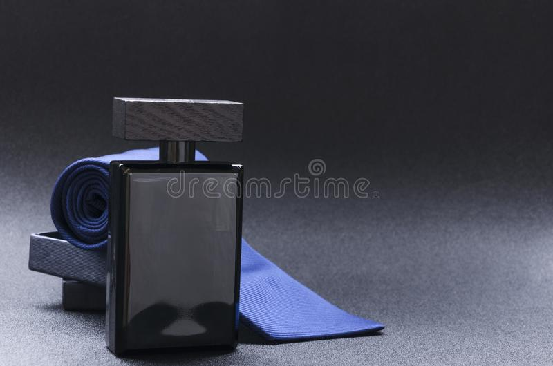 Black bottle of cologne for men, blue tie on the black background royalty free stock photo