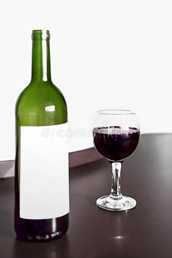 Open bottle and one glass of red wine on brown wodden table and white blurred wall background. Alcohol drink on desk in room. Mock. Up for wine label royalty free stock images