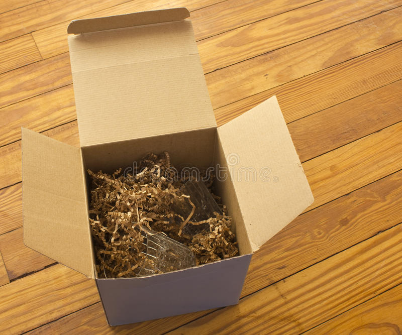 Open box with packing paper shreds. An open box with packing paper shreds sitting on a wooden table with crystal glasses inside royalty free stock photography