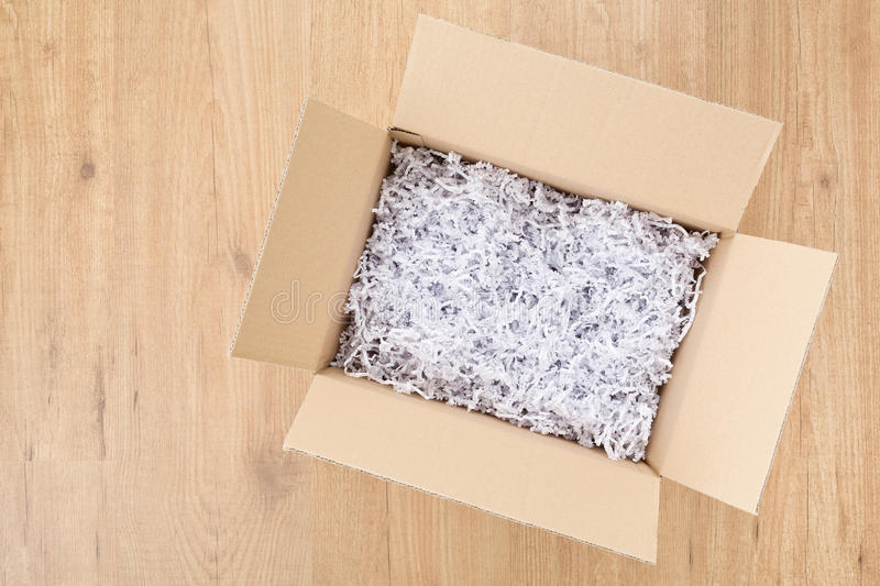 Open Box or Parcel on the Floor. An open box with filling material inside lying on a laminated wooden floor, top view with copy space royalty free stock images