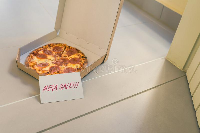 Open box of pizza and card with text: mega sale on home doorstep on front porch. Delivery. Concept. royalty free stock photography