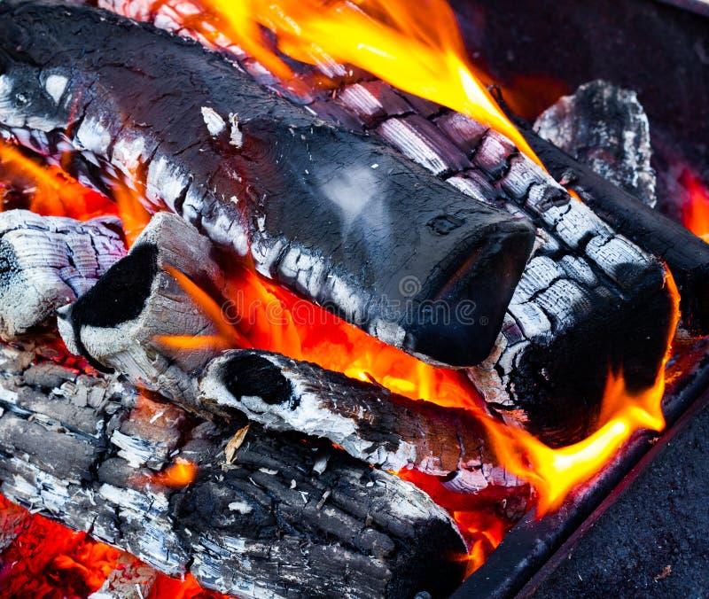 Open brand dichte omhooggaande, brandende brandhout, steenkool en as Brand in een open open haard stock afbeeldingen