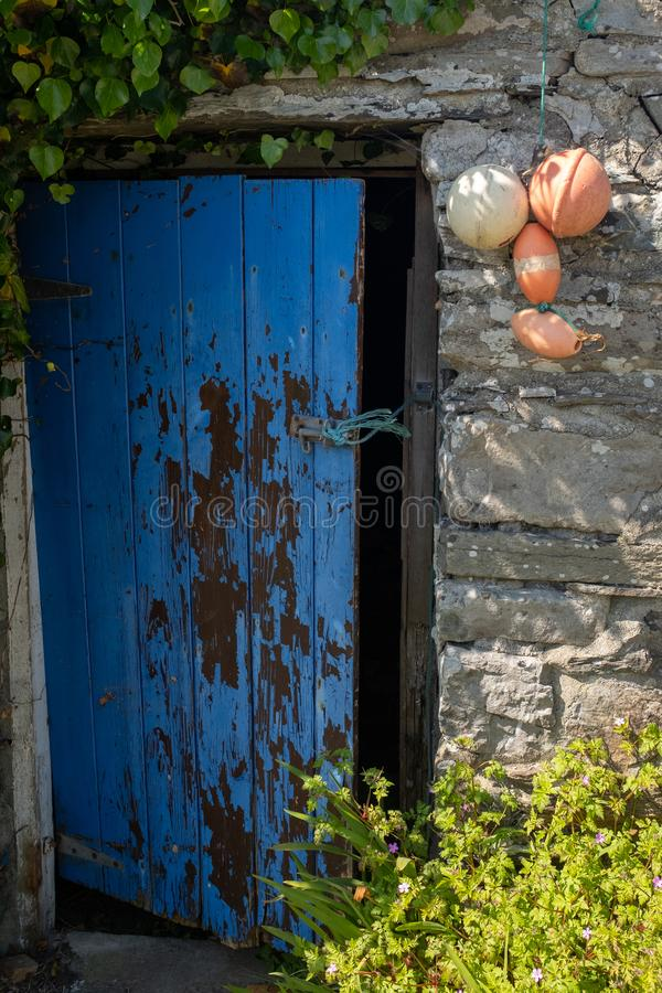 An open broken painted door held open with a piece of string of a traditional stone building in Ireland royalty free stock photos