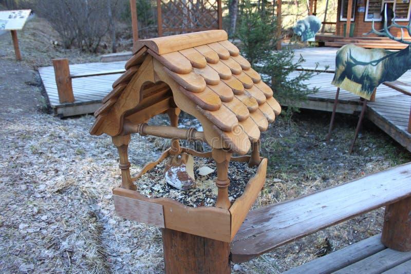 An open brown bird feeder installed on the railings in the Krasnoyarskie stolby national reserve stock image