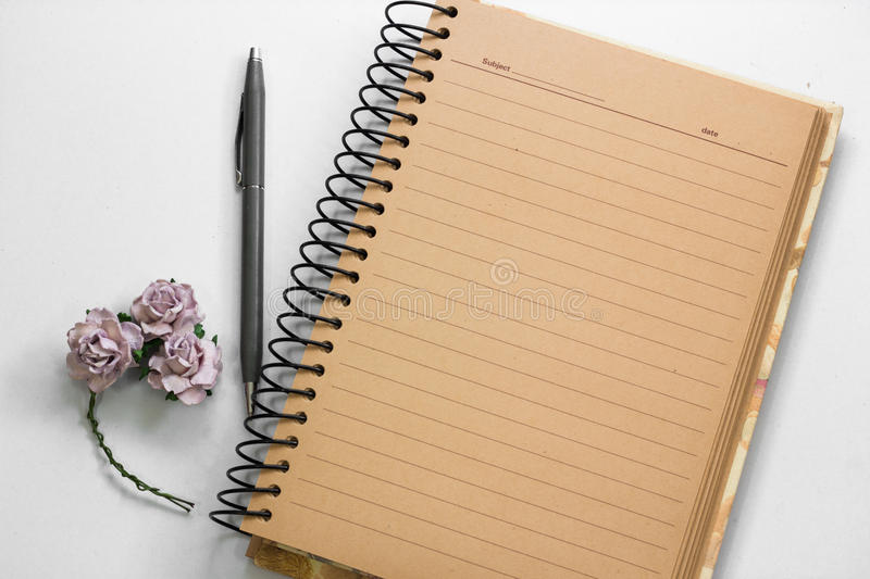 Open brown paper note book with lined and gray pen on white back stock photo