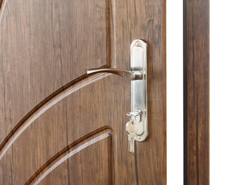 Open brown wooden door handle with lock. Open door handle. Door lock with keys. Brown wooden door closeup isolated. Modern interior design, door handle. New stock photos