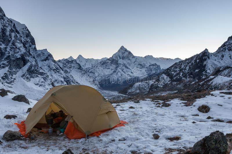 Open camping tent with kitchen stuff in snowy. Open camping tent with kitchen stuff in snowy mountains with snowy peak of Ama Dablam on the background in royalty free stock images
