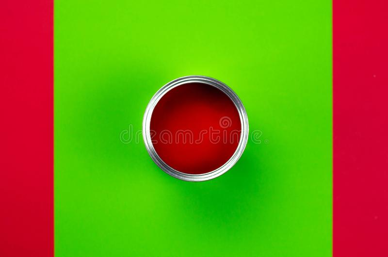 An open can of red paint on a green-red background royalty free stock photos