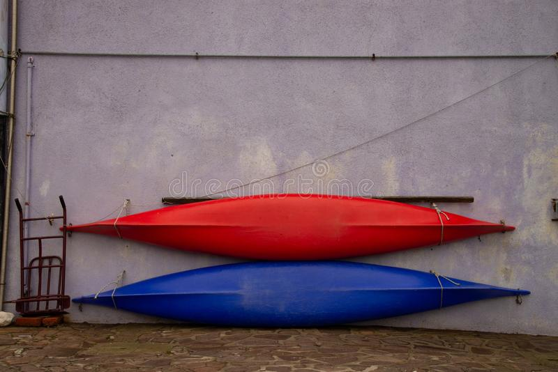 Two red and blue canoes resting on the wall, ready for the first exit into the sea. Open canoes ideal for recreational activities, sports, water tourism stock photos