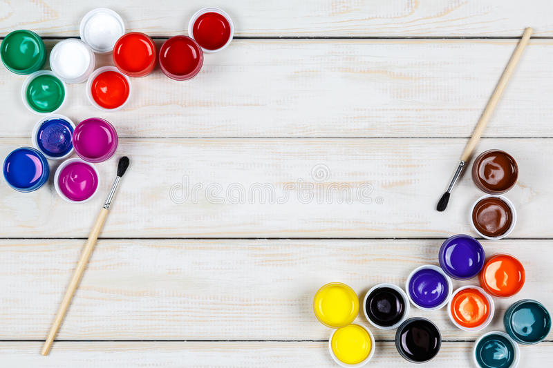 Open cans of colored paint with two brushes on the white wooden royalty free stock photo