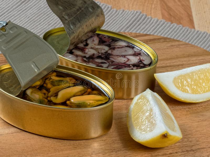 Open cans of preserved seafood. Cans of preserves with mussels and octopus on a rustic wooden board, with lemon slices and toothpicks stock photo