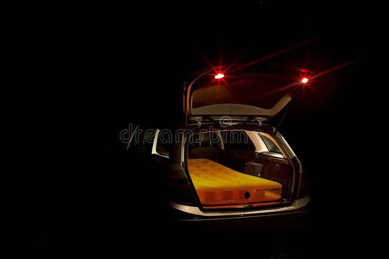 Open car boot with mattress. Night view of an illuminated open car boot on an estate car or station wagon with a mattress inside royalty free stock photography