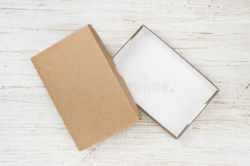 Open cardboard box with cover on wooden table, above view.  royalty free stock photos