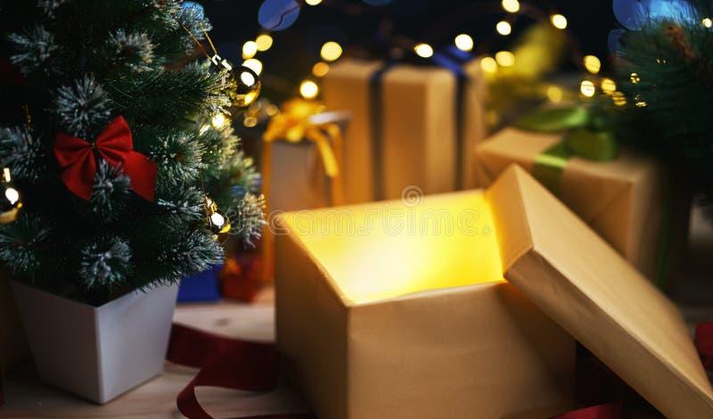Open Christmas Box Gift Besides Small Christmas Tree. Glowing Li royalty free stock image