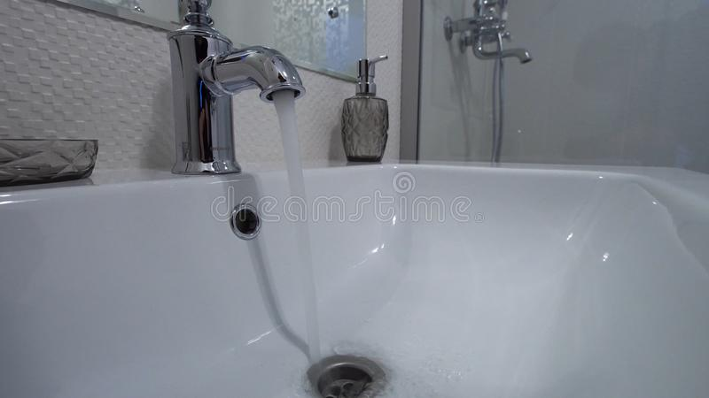 Open chrome faucet washbasin. Water flows from the tap in the modern bathroom stock photos