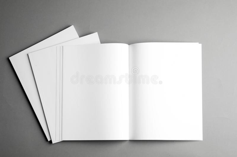 Open and closed blank brochures on grey background, top view. Mock up for design royalty free stock images