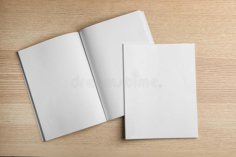 Open and closed blank brochures on wooden background, top view. Mock up for design royalty free stock photos