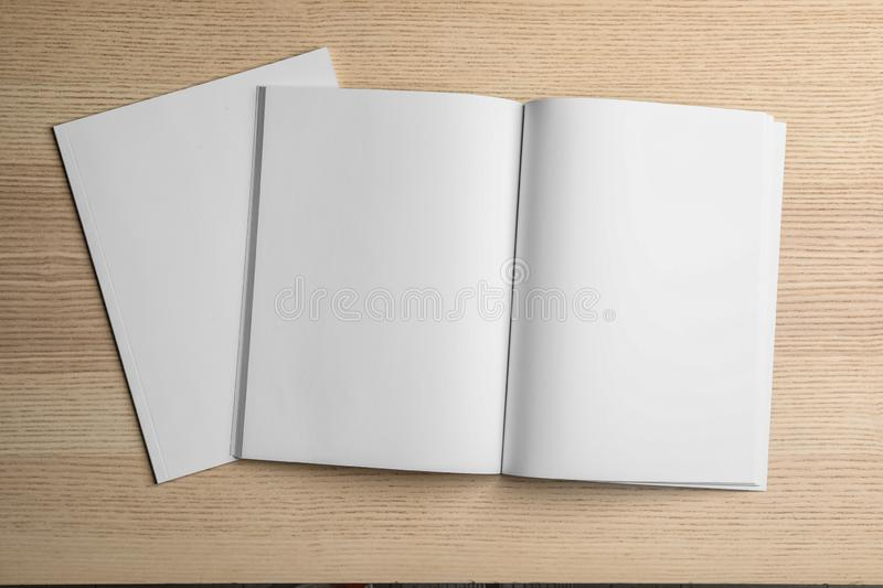 Open and closed blank brochures on wooden background, top view. Mock up for design stock photos