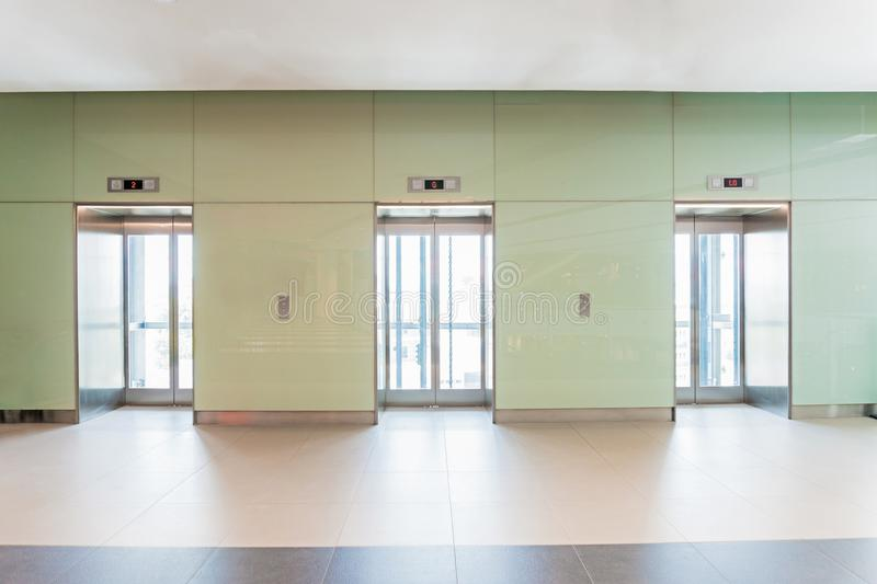 Open and closed chrome metal office building elevator doors. stock photography