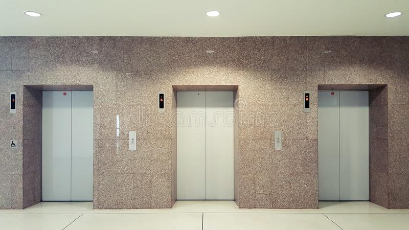 Open and closed chrome metal office building elevator doors realistic photo. Lift transportation floor to floors with push switch. For up and down. Elevator stock photo