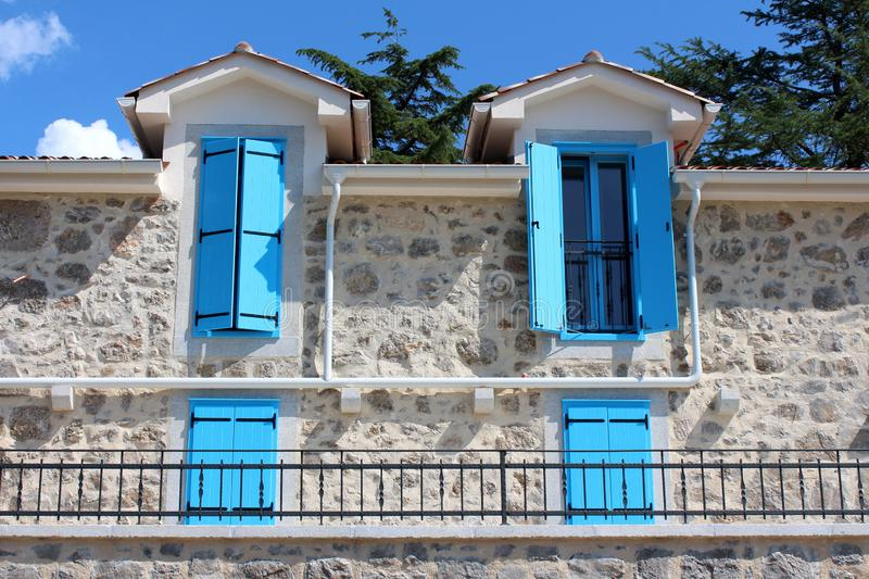 Open and closed light blue wooden window blinds on windows of newly built Mediterranean villa in traditional stone style with stock image
