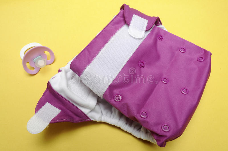 Open Cloth Diaper with Dummy on Yellow Background stock photos