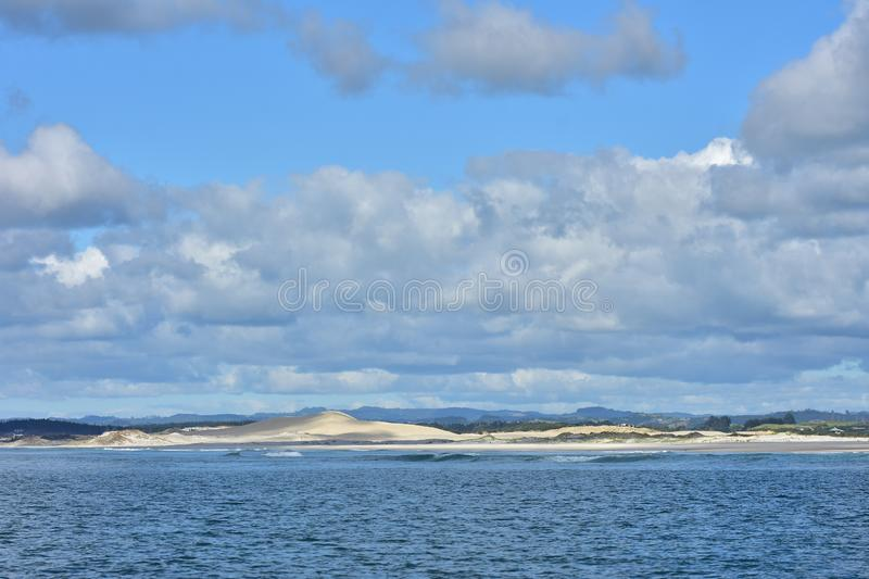 Northland coast of sand dunes. Open coast with large sand dunes partially covered by native vegetation in Northland and partially cloudy but otherwise blue sky stock images
