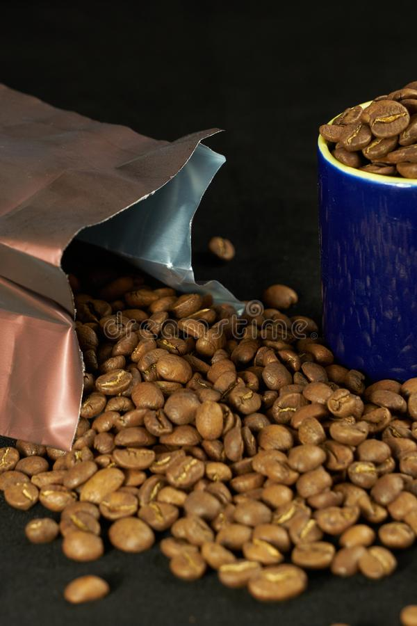 An open coffee pack with all the beans strewn, next to a cup of full blue coffee. The assembly is isolated on a black background royalty free stock photography