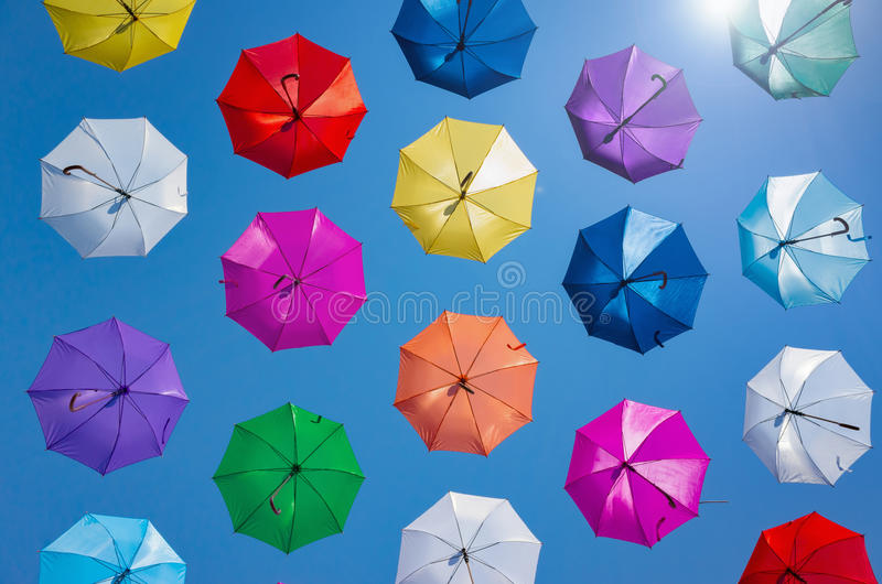 Open colorful umbrellas flying in clear blue sky. Hot sunny summer day, beautiful weather royalty free stock images