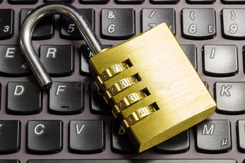 Open combination padlock on a laptop keyboard symbolizing data security. Open combination padlock on a laptop keyboard symbolizing data, computer and business stock photo