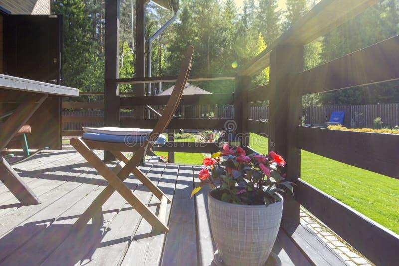 Open comfortabel terras van natuurlijk hout in moderne binnenplaats van buitenhuis Bloemen in potten op zonnige ochtend, op tuina stock foto