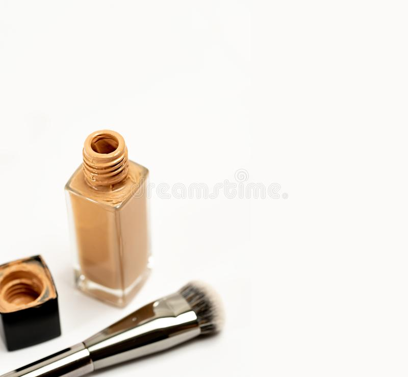 An Open Cosmetic Foundation Bottle with Blur Cap and Brush on White Background. Selective royalty free stock photo