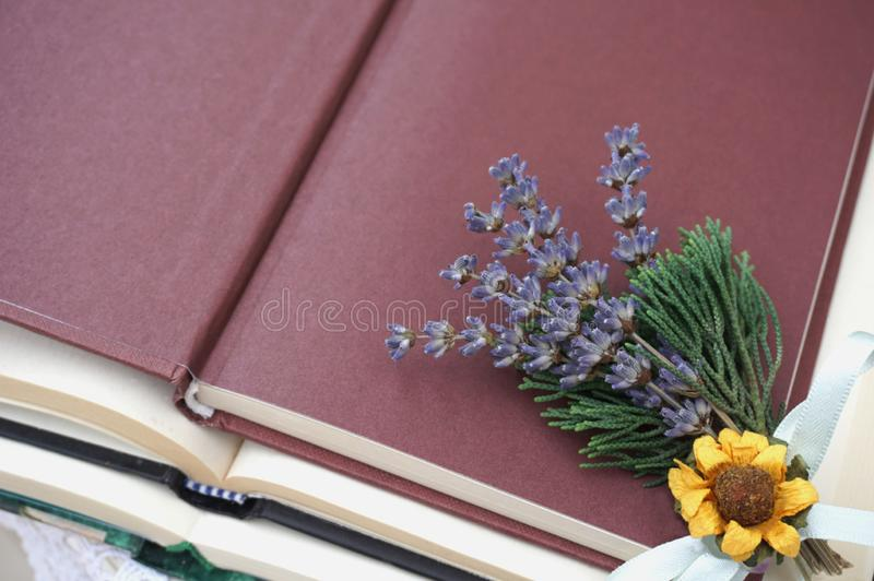 Open cover of book with small bunch of lavender, dry sunflower and green branches royalty free stock photo